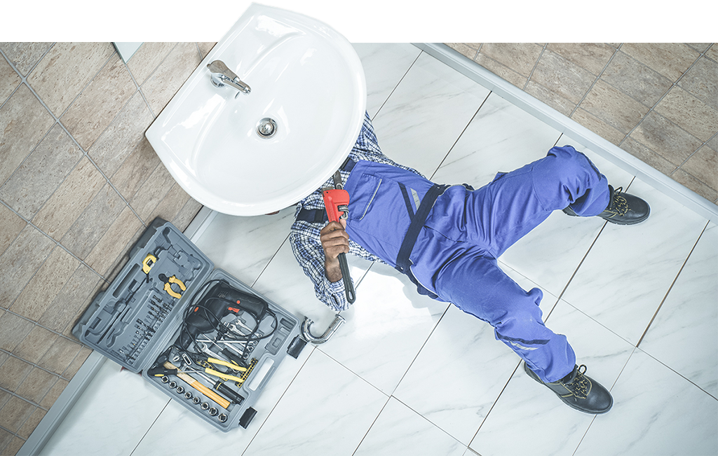 Homme sous un lavabo en faïence - plomberie